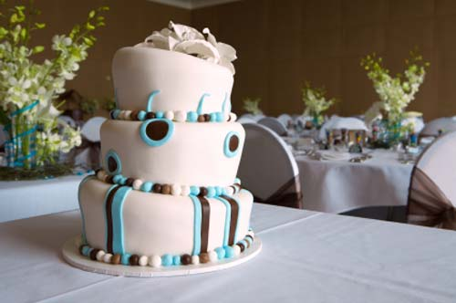 white topsy turvy novelty mad hatter wedding cake, decorated with light blue and brown crazy fondant shapes
