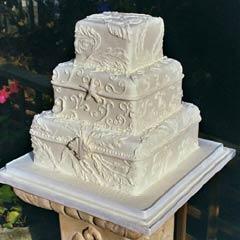 Three tier Victorian white intricate designer wedding cake