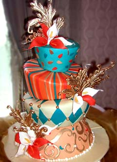 Harlequin, stripe and swirl wedding cake decorated with blue, orange, peach and white fondant patterns