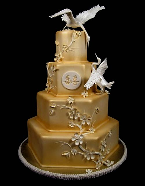 Four tier hexagon Asian style gold wedding cake decorated with gold cherry blossom decorations