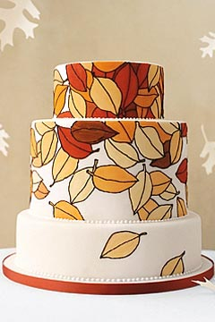 Three tier white wedding cake painted or airbrushed autumn leaves cascading down from the top tier