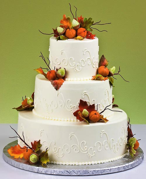Large three tier autumn theme wedding cake decorated with white buttercream scroll work, hand crafted orange fondant autumn leaves