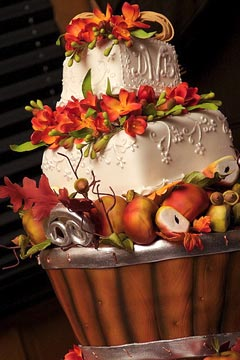 Two tier square wedding cake decorated with earth tone autumn orange coloured flowers