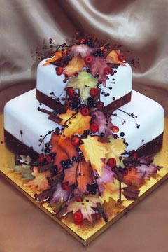 White two tier square autumn leaves wedding cake decorated with red berries and cherries