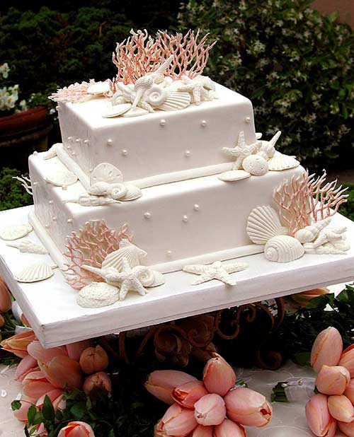 Stunning two tier white wedding cake decorated with orange coral, white edible seashells