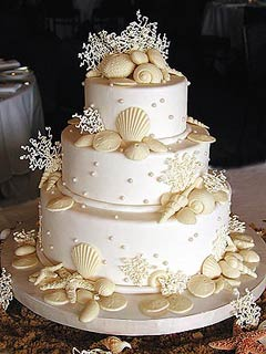 Three tier ivory wedding cake decorated with white chocolate seashells