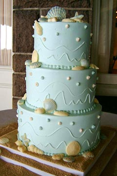 Three tier light blue wedding cake, decorated with edible white and blue seashells