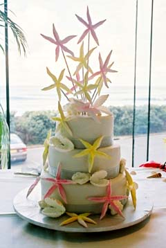 Three tier beach sea shell cake decorate with yellow, pink and white star fish and seashells
