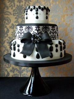 Round three tier black and white art deco wedding cake, featuring a large black fondant bow with a black brooch, dangling black beads and crystals