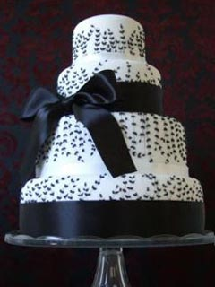 Classic round four tier white and black theme wedding cake decorated with black fern patterns, large black ribbon with a bow in the centre