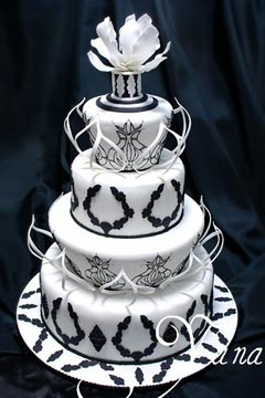 Stunning black and white, four tier retro wedding cake decorated with white and black shapes and patterns