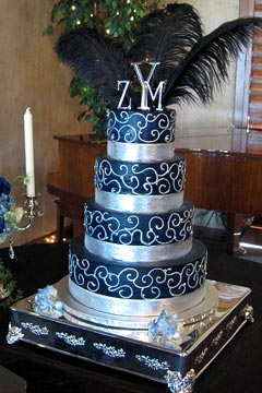 Four tier black and silver round wedding cake decorated with silver scrolls