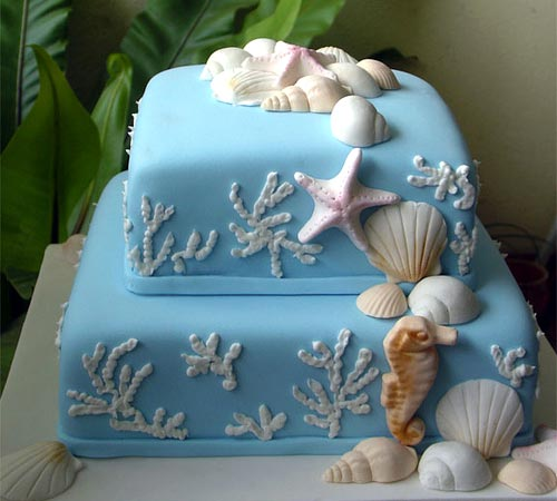 Two tier, square blue beach them and seashell wedding cake