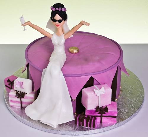 Novelty, round purple bridal shower cake with a bride wedding cake topper. Decorated with small and purple and pink wedding gifts