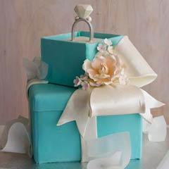 Two tier, Tiffany Blue gift box bridal cake design, decoated with white fondant ribbon and a handmade diamond engagement ring wedding cake topper