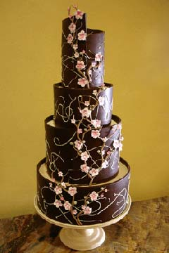 Tall creative four tier brown and pink cherry blossom wedding cake decorated with pink cherry blossoms