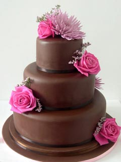 Three tier brown fondant wedding cake decorated with pink roses
