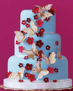 Three tier blue wedding cake decorated with handmade gum paste butterflies in white with gold