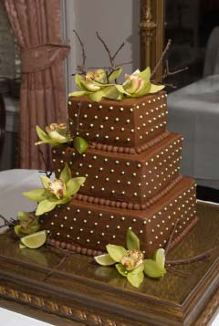 Three tier square chocolate brown wedding cake decorated with green cymbidium orchids