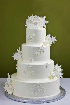 Simple four tier, winter white Christmas snowflake wedding cake is decorated with large snow white handcrafted and edible cascading snowflakes
