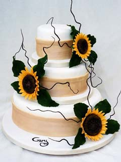 Three tier country style sunflower cake decorated with peachy coloured organza ribbon around each tier