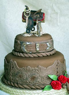 Brown two tier western style wedding cake decorate with intricate western designs and saddle wedding cake topper