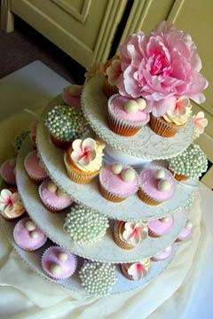 Four tiered white and pink wedding cupcakes