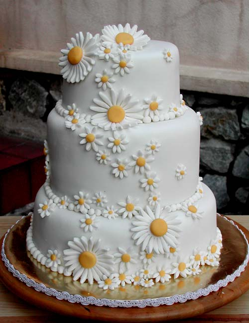 three tier round white wedding cake covered with small and large intricate white hand made fondant dasies