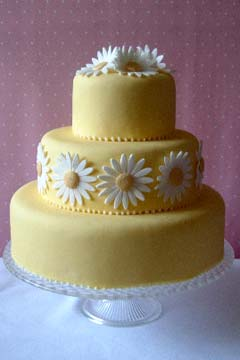 Three tier yellow fondant wedding cake decorated with hand made gum past white and yellow daisies