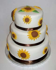 three tier round wedding cake decorated with yellow handmade fondant daisies