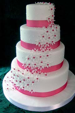 Four tier white and pink fondant wedding cake decorated with sugar paste white & pink daisies
