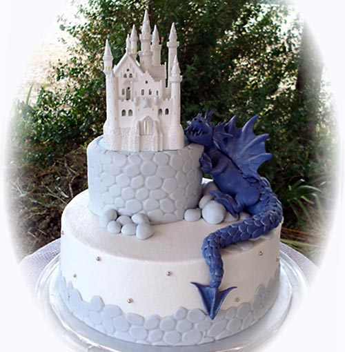 Amazing two tier, white and light blue castle wedding cake with a electric blue dragon climbing up the the white castle