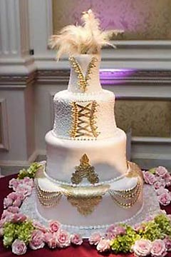 A bridal gown cake designed to look like the brides wedding dress. Decorated with gold accents and white feather