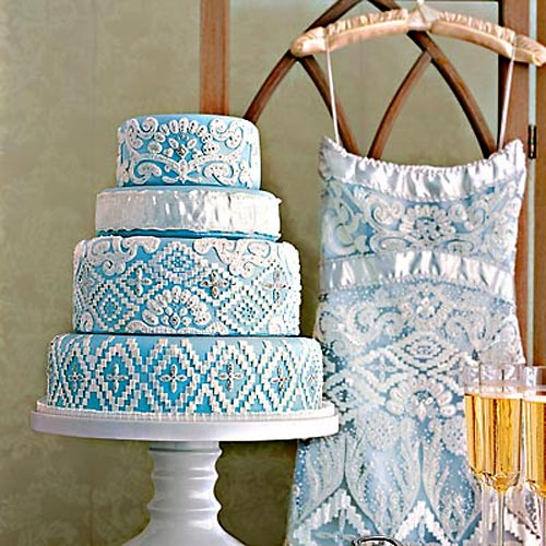 Four tier white and blue wedding dress cake make to look like the brides gown. Onately decorated to show the lacy layer of the gown