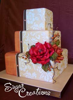 Fancy three tier square retro orange and ivory wedding cake. Decorated with white embosed wall paper like decorations
