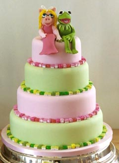 A novelty four tier pink and green wedding cake of Miss Piggy and Kermit the frog