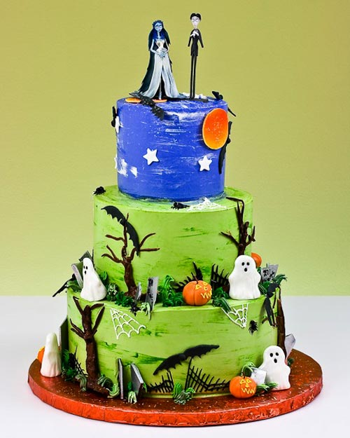 Three tier, spooky blue and green halloween wedding cake with a graveyard theme,  decorated with white ghosts, spider webs and spooky orange pumpkin head