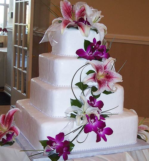Square four tier white fondant wedding cake decorated with tropical flowers, like purple orchids, white oriental lillies and pink tiger lillies