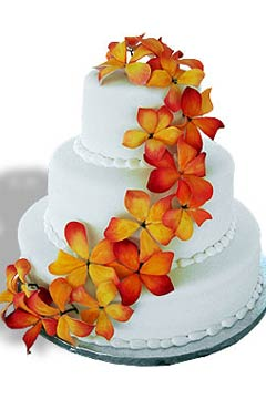 Three tier round fondant wedding cake design decorated with orange tropical Hawaiian flowers