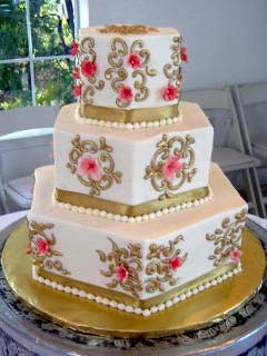 Three tier white, gold and pink retro hexagonal shaped wedding cake