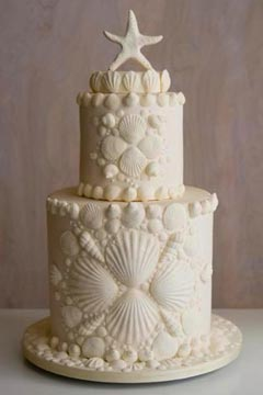 Two tier ivory seashells, beach theme wedding cake. Decorated with seashell patterns an a starfish wedding cake topper
