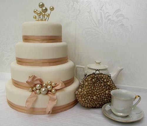 Four tier, 1940's style ivory wedding cake, decorated with champagne and gold coloured organza ribbon and pearl accents