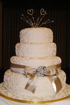 Elegant three tier wedding cake decorted with ivory swirls and champagne coloured satin bow and ribbon