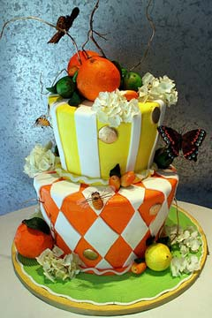Two tier yellow and orange citrus theme wedding cake in the shape of a mad hatter design