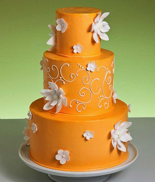 Three tier bright orange wedding cake, covered with orange buttercream