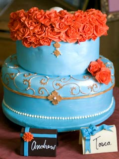 Two tier round blue fondant wedding cake decoated with orange roses