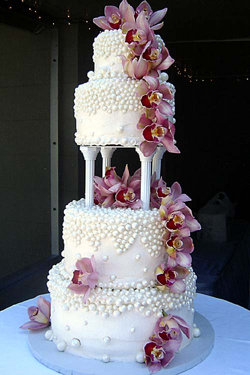 Huge gorgeous four tier round shaped wedding cake garnished with pink Cymbidium Orchids