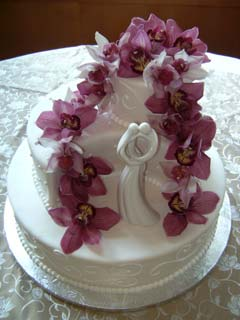 Unusually shaped wedding cake with cascading pink Cymbidium Orchids