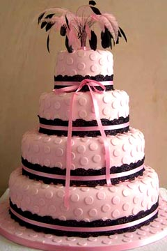 Pink four tier polka dot wedding decorated with black lace and pink and black feather wedding cake topper