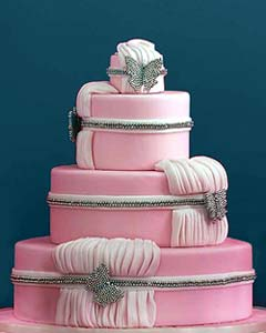 Very feminine, three tier round pink fondant wedding cake with draped pink gathered fondant. Decorated with diamontee butterfly brooches